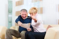 Aînés à la maison recevant une bonne lettre Image stock