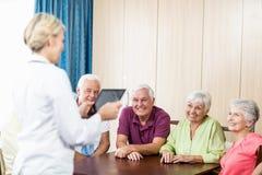 Aînés écoutant l'infirmière avec le comprimé Images libres de droits