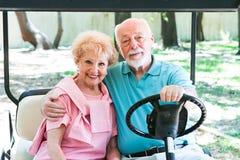 Aînés actifs dans le chariot de golf Photos libres de droits