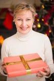 Aînés actifs de sourire tenant un cadeau à Noël Photo libre de droits