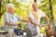 Aînés actifs faisant un cycle en parc Photos stock