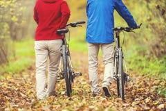 Aînés actifs marchant avec le vélo Photo stock