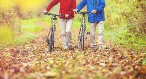 Aînés actifs marchant avec le vélo Image libre de droits