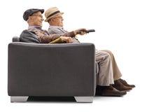 Aînés assis à une télévision de observation de sofa Photo libre de droits