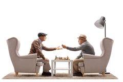 Aînés assis dans des fauteuils jouant une partie d'échecs et une argumentation Photos stock