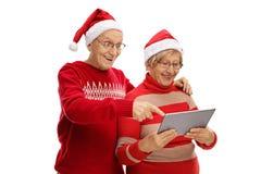 Aînés avec des chapeaux de Santa regardant un comprimé Photos libres de droits