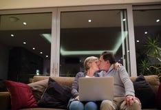 Aînés avec l'ordinateur portable se reposant sur un divan, embrassant Photo libre de droits