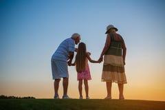 Aînés avec l'petit-enfant, coucher du soleil Photographie stock libre de droits