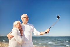 Aînés avec le smartphone prenant le selfie sur la plage Image stock