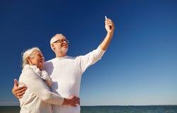 Aînés avec le smartphone prenant le selfie sur la plage Photo stock