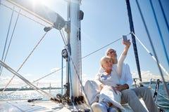 Aînés avec le smartphone prenant le selfie sur le yacht Photo stock