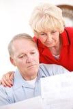 Aînés : Couples contrariés au montant de factures Photographie stock
