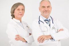 Aînés d'équipe médicale restant les bras en travers ensemble Photographie stock