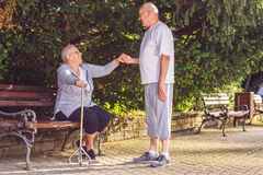 Aînés dans l'épouse de soin d'homme plus âgé de parc en parc Images stock