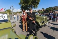 Aînés dans l'uniforme militaire se tenant près de rétros voitures de la deuxième guerre mondiale Images stock
