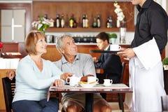 Aînés de portion de serveur dans le café Image libre de droits