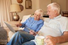 Aînés de sourire passant en revue l'Internet sur leur sofa à la maison Photos libres de droits