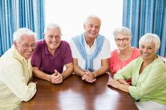 Aînés de sourire s'asseyant à la table Image stock