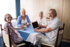Aînés de sourire s'asseyant avec des technologies à la table Photo libre de droits
