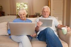 Aînés de sourire s'asseyant sur leur sofa passant en revue l'Internet Photo libre de droits