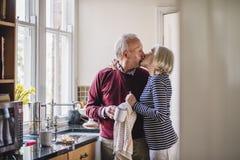 Aînés embrassant dans la cuisine Photos libres de droits