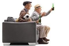 Aînés enthousiastes observant le football à la télévision et ayant une abeille Images stock