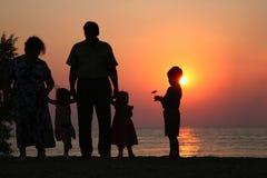 Aînés et enfants sur le coucher du soleil Images stock