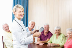 Aînés et infirmière de sourire tenant un comprimé Photo libre de droits