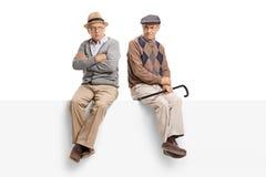 Aînés fâchés s'asseyant sur un panneau Image stock