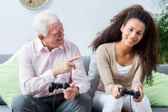 Aînés gagnant en jeux vidéo avec la jeunesse Images libres de droits