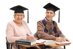 Aînés gais avec des chapeaux d'obtention du diplôme se reposant dans des chaises d'école Photographie stock