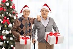 Aînés gais avec des présents devant un arbre de Noël Photographie stock libre de droits