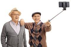 Aînés gais prenant un selfie avec un bâton de selfie Images libres de droits