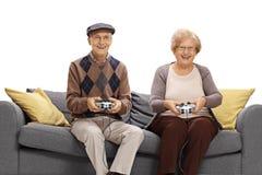 Aînés gais s'asseyant sur un sofa et jouant des jeux vidéo Photographie stock libre de droits