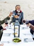 Aînés grillant avec le vin rouge à la plage Image libre de droits