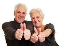 Aînés heureux affichant des pouces vers le haut Photographie stock libre de droits