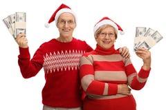 Aînés heureux avec des chapeaux de Noël et paquets d'argent d'isolement dessus Image stock