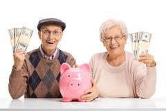 Aînés heureux avec des paquets d'argent et une tirelire Images libres de droits