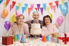 Aînés heureux avec un gâteau et des chapeaux de partie Photos libres de droits