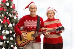 Aînés heureux jouant une guitare devant un arbre de Noël Photographie stock libre de droits