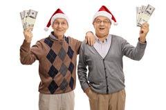 Aînés heureux utilisant des chapeaux de Noël et tenant des paquets de mone Photos libres de droits