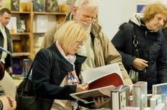 Aînés intelligents lisant de nouveaux livres avec l'intérêt sur le festival de livre Photographie stock