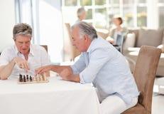 Aînés jouant aux échecs dans la salle de séjour Photo libre de droits
