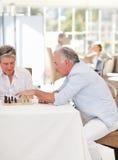 Aînés jouant aux échecs dans la salle de séjour Images libres de droits