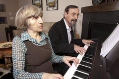 Aînés jouant le duet de piano Images stock