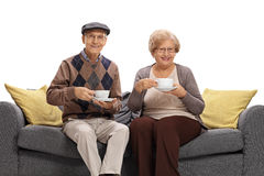 Aînés joyeux avec des tasses se reposant sur un sofa et regardant le Ca Image libre de droits