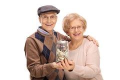 Aînés joyeux tenant un pot avec l'argent Image stock