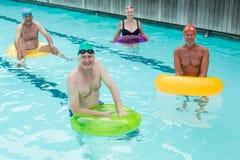 Aînés nageant avec les anneaux gonflables dans la piscine Photos stock