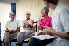 Aînés parlant avec l'infirmière au sujet du médicament Photo libre de droits