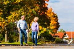 Aînés pendant l'automne ou l'automne marchant main dans la main Image libre de droits